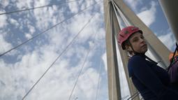 """Koreografer dan penari """"ekstrem"""", Katerina Soldatou turun ke bawah  jembatan Rio-Antirio untuk melakukan tarian di Yunani selatan, Senin (12/3).  Jembatan ini merupakan jembatan bentang kabel terpanjang di dunia. (AP Photo/Petros Giannakouris)"""