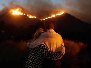 Roger Bloxberg dan istrinya, Anne berpelukan saat menyaksikan kebakaran di puncak bukit dekat rumah mereka di West Hills, California, AS, Jumat (9/11). Api Woolsey melahap ribuan hektare hutan dan menghancurkan banyak rumah. (AP Photo/Marcio Jose Sanchez)