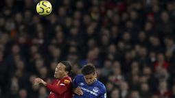 Bek Liverpool, Virgil van Dijk (kiri) berebut bola udara dengan pemain Everrton, Dominic Calvert-Lewin  pada pertandingan lanjutan Liga Inggris di Stadion Anfield, Rabu (4/12/2019). Liverpool menang telak 5-2 atas Everton. (AP Photo/Jon Super)