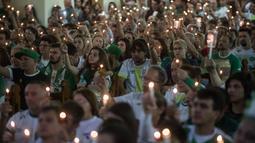 Ribuan fans dan kelurga korban pesawat Lamia 2933 menyalakan lilin memperingati satu tahun kecelakaan di Arena Conda stadium, Chapeco, Santa Catarina, Brasil, (28/11/2017). Sekitar 19 pemain Chapecoense meninggal. (AFP/Nelson Meida)