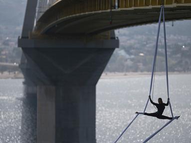 """Seorang koreografer dan penari """"ekstrem"""", Katerina Soldatou melakukan tarian di bawah jembatan Rio-Antirio, Yunani selatan, Senin (12/3).  Jembatan ini merupakan jembatan bentang kabel terpanjang di dunia. (AP Photo/Petros Giannakouris)"""