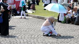 Peserta aksi memunguti ceceran sampah di halaman Monumen Nasional usai aksi, Jakarta, Jumat (11/5). Ribuan massa melakukan aksi menyoroti konflik Palestina dan Israel pada perebutan bangunan suci atau Baitul Maqdis. (Liputan6.com/Helmi Fithriansyah)