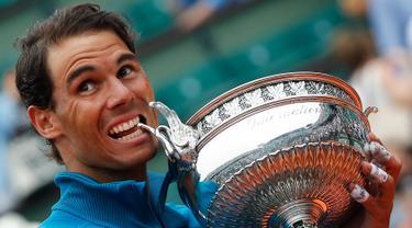 Petenis Spanyol, Rafael Nadal menggigit pialanya setelah mengalahkan Dominic Thien dari Austria pada partai final Prancis Terbuka di Stadion Roland Garros, Minggu (10/6). Ini merupakan trofi ke-11 Prancis Terbuka yang diraih Nadal. (AP/Michel Euler)