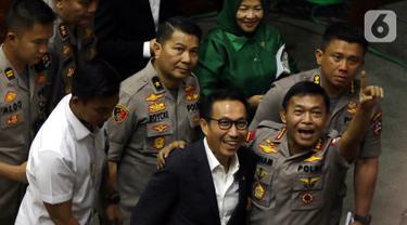 Komjen Pol Idham Azis (kanan) mengacungkan jari kepada wartawan setelah ditetapkan sebagai Kapolri dalam rapat paripurna di Kompleks Parlemen, Jakarta,  Kamis (31/10/2019). DPR menyetujui Idham Aziz menjadi Kapolri menggantikan Jenderal Polisi (Purn) Tito Karnavian. (Liputan6.com/JohanTallo)