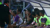 Johan Prasetyo menyampaikan instruksi pelatih Budihardjo Thalib lewat headset ponsel kepada asisten Alfiat saat laga Persik kontra Persis di Stadion Brawijaya, Kota Kediri, Jumat (6/9/2019). (Bola.com/Gatot Susetyo)