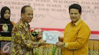Menristek Dikti, Mohammad Nasir (kiri) bertukar cinderamata dengan Ketua KPU, Husni Kamil di Kantor KPU, Jakarta, Kamis (30/7/2015). Penandatangan terkait kerjasama verifikasi ijazah dalam rangka Pilkada serentak. (Liputan6.com/Faizal Fanani)