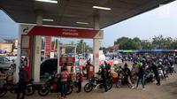 Pemudik sepeda motor mengantre BBM di SPBU Tulungangung, Indramayu, Jabar, Jumat (23/6). Tingginya volume kendaraan pemudik yang masuk membuat antrian menjadi panjang. (Liputan6.com/Johan Tallo)