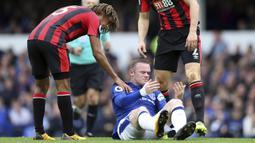 Striker Everton, Wayne Rooney, mengalami pendarahan di mata kirinya usai duel udara dengan bek Bournemouth, Simon Francis, pada Premier League, di Stadion Goodison Park, Sabtu (23/9/2017). Everton menang 2-1 atas Bournemouth. (AP/Barrington Coombs)