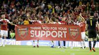 Para pemain Arsenal membawa spanduk menyapa suporter usai pertandingan melawan Chelsea pada  International Champions Cup (ICC) di Stadion Aviva di Dublin (1/8). Arsenal menang atas Chelsea lewat adu penalti 6-5. (AFP Photo/Paul Faith)