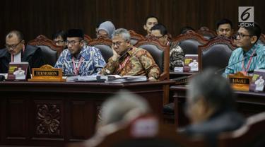 Ekspresi Ketua KPU Arief Budiman (tengah) saat mengikuti sidang sengketa Pilpres 2019 di Gedung MK, Jakarta, Selasa (18/6/2019). Sidang tersebut beragendakan mendengarkan jawaban dari termohon. (Liputan6.com/Faizal Fanani)