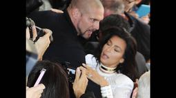Kim Kardashian terlihat hampir jatuh ke tanah saat tiba-tiba diterjang seorang fans di Paris, (25/9/14). (Dailymail)