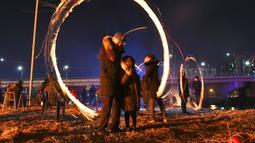 Warga Korea Selatan memutar kaleng arang yang terbakar selama perayaan  Bulan Purnama pertama tahun baru Imlek di Seoul (17/2). Permainan ini dipercaya dapat menyuburkan tanah dan menyingkirkannya hama. (AFP Photo/Jung Yeon-je)