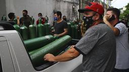 Antrean keluarga pasien COVID-19 yang dirawat di rumah sakit dengan membawa tangki oksigen kosong untuk mengisi kembali di Manaus, negara bagian Amazonas, Brasil, 15 Januari 2021. Negara Bagian Amazonas di Brasil kehabisan oksigen karena semakin melonjaknya pasien Covid-19. (AP Photo/Edmar Barros)