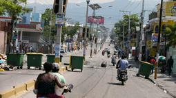 Tempat sampah memblokir jalan raya saat terjadi protes krisis bahan bakar di Port-au-Prince, Haiti, Senin (16/9/2019). Krisis bahan bakar menyebabkan transportasi umum tidak beroperasi. (AP Photo/Dieu Nalio Chery)
