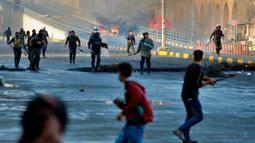 Pasukan keamanan berusaha membubarkan demonstran antipemerintah saat bentrokan di Najaf, Irak, Kamis (28/11/2019). Kerusuhan di Ibu Kota dan wilayah selatan Irak terus meningkat setelah pembakaran gedung Konsulat Iran. (AP Photo/Anmar Khalil)