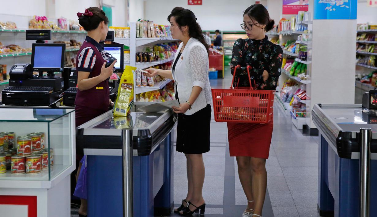 Dua wanita berada di kasir di supermarket di Pyongyang, Korea Utara (12/9). Banyak produk dalam negeri terlihat di rak-rak supermarket tersebut sebagai bagian dari upaya membangun ekonominya dan meningkatkan standar hidup nasional. (AP Photo/Kin Cheung)