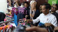 Presiden Joko Widodo (Jokowi) mengajak Direktur Pelaksana IMF Christine Lagarde memilih batik saat mengunjungi  Blok A Pasar Tanah Abang, Jakarta, Senin (26/2). Keduanya meninjau beberapa kios sambil berbincang dengan penjual. (Liputan6.com/Angga Yuniar)
