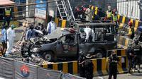 Petugas keamanan menjaga mobil van polisi yang rusak usai ledakan bom di luar tempat suci umat muslim Sufi, Lahore, Pakistan, Rabu (8/5/2019). Kebanyakan militan menganggap masjid Sufi dan ritual yang sering dilakukan di makam nabi sebagai hal 'tidak Islami.' (AP Photo/K.M. Chaudary)