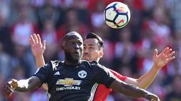 Striker Manchester United, Romelu Lukaku, duel udara dengan bek Southampton, Maya Yoshida, pada laga Premier League di Stadion St Mary's, Sabtu (23/9/2017). Manchester United menang 1-0 atas Southampton. (AFP/Glyn Kirk)