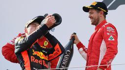 Pembalap Red Bull Max Verstappen meminum sampanye bersama dengan pembalap Ferrari, Sebastian Vettel dari Australia setelah berhasil memenangkan GP Austia di Red Bull Ring, Spielberg, Austria, (1/7). (AP Photo / Ronald Zak)