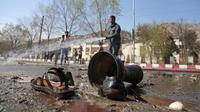 Petugas pemadam kebakaran membersihkan lokasi pemboman bunuh diri di dekat Universitas Kabul, Afghanistan, (21/3). Pembom bunuh diri itu menyerang di jalan menuju kuil Syiah di ibukota Afghanistan. (AP Photo/Rahmat Gul)