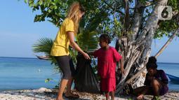 Aktivis AS, Carrie dan anak-anak membersihkan sampah plastik di bibir pantai Desa Sawandarek, Raja Ampat, Papua Barat (22/11/2019). Aksi membersihkan sampah plastik ini, digagas Carrie, aktivis asal Amerika Serikat,  yang sudah menetap di Indonesia selama 3 tahun. (Liputan6.com/Herman Zakharia)