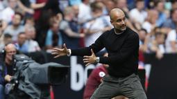 Pelatih Manchester City, Pep Guardiola, memberikan instruksi saat melawan West Ham pada laga Premier League di Stadion London, London, Sabtu (10/8). West Ham kalah 0-5 dari City. (AFP/Ian Kington)