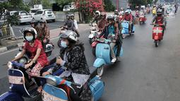 Anggota komunitas Vespa se-Jabodetabek saat konvoi dalam rangka memperingati Hari Kartini di Jakarta, Minggu (21/4). Dalam konvoi ini para pengendara vespa mengenakan kebaya bagi perempuan dan batik serta lurik bagi laki-laki. (merdeka.com/Iqbal Nugroho)