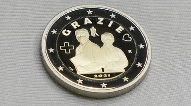 Koin 2 Euro yang didedikasikan untuk profesi tenaga kesehatan yang memerangi pandemi Covid-19 di percetakan uang negara Italia, di Roma, Kamis (21/1/2021). Koin itu bergambar seorang pria dan perempuan mengenakan seragam medis dan masker serta tulisan 'Grazie' atau Terima Kasih (AP/Andrew Medichini)