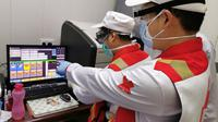 Anggota tim pakar medis China, Chen Huai (depan) dan Ai Hexu memeriksa citra tomografi terkomputasi dada di Baghdad, Irak, Senin (30/3/2020). Sejak 7 Maret lalu, tujuh pakar medis China bekerja sama dengan tenaga ahli lokal di Irak untuk memerangi epidemi virus corona COVID-19. (Xinhua)
