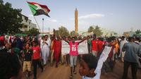 Warga Sudan menyanyikan slogan dan mengibarkan bendera nasional saat mereka merayakan kemenangan di Khartoum (Ashraf Shazly / AFP)