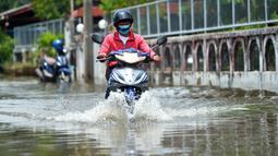 Seorang pria mengendarai sepeda motor di sebuah jalan yang terendam banjir pascahujan lebat di Bangkok, Thailand (31/8/2020). (Xinhua/Rachen Sageamsak)