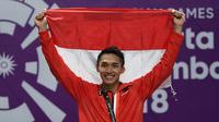 Jonatan Christie tersenyum sambil mengibarkan bendera Merah Putih saat upacara penghargaan cabang olahraga badminton Asian Games 2018, Jakarta, Selasa (28/8). Jonatan menang tiga set langsung 21-18, 20-22, dan 21-15. (AFP Photo/Sonny Tumbelaka)