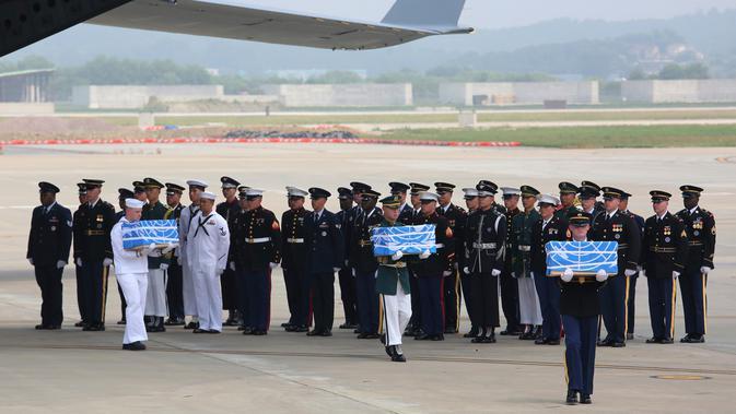 Pasukan PBB membawa kotak berisi jenazah yang diyakini sebagai tentara Amerika Serikat (AS) yang tewas selama Perang Korea pada tahun 1950-1953 di Pangkalan Udara Osan, Pyeongtaek, Korea Selatan, Jumat (27/7). (AP Photo/Ahn Young-joon, Pool)