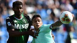 Striker Inter Milan, Lautaro Martinez, berebut bola dengan bek Sassuolo, Marlon, pada laga Serie A Italia di Stadion Mapei, Reggio-Emilia, Minggu (20/10). Sassuolo kalah 3-4 atas Inter. (AFP/Miguel Medina)
