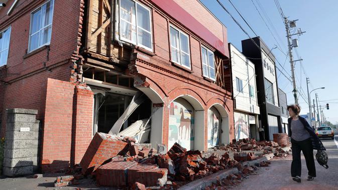 Seorang warga melihat kondisi bangunan yang rusak akibat gempa mengguncang Kota Abira di Hokkaido, Jepang, Kamis (6/9). Bencana ini telah menewaskan sedikitnya dua orang dan puluhan lainnya masih dalam proses pencarian. (Masanori Takei/Kyodo News via AP)