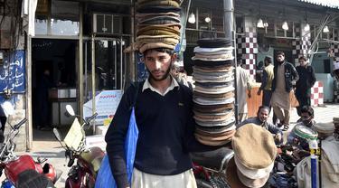 Seorang penjual menjajakan topi tradisional di sebuah jalan di Peshawar, Pakistan barat laut, pada 28 Desember 2020. Topi tradisional yang terbuat dari bahan wol ini sangat populer di kalangan warga Pakistan selama musim dingin. (Xinhua/Saeed Ahmad)