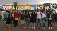 Keluarga membawa tulisan 'Welcome Home' saat menunggu WNI yang selesai menjalani observasi virus corona dari Natuna, di Bandara Halim Perdanakusuma, Jakarta, Sabtu (15/2/2020). Pemerintah resmi memulangkan 238 WNI ke daerah masing-masing karena telah dinyatakan sehat. (Liputan6.com/Herman Zakharia)
