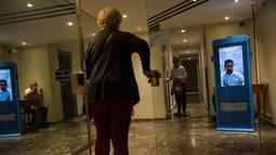 Seorang wanita memasuki sebuah gedung di Buenos Aires, Argentina, Senin (23/4). Penjaga keamanan virtual memantau setiap pengunjung yang ingin keluar masuk gedung. (AP Photo/Rodrigo Abd)
