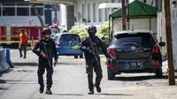 Aparat kepolisian bersenjata lengkap berjaga setelah serangan bom bunuh diri di Polrestabes Surabaya, Jawa Timur, Senin (14/5). Polisi mendata ada 10 korban luka dalam tragedi bom bunuh diri di Markas Polrestabes Surabaya. (AFP/JUNI KRISWANTO)