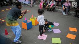 Anak-anak bermain permainan tradisional ditemani sejumlah mahasiswa dari Penggerak Olahraga saat car free day (CFD) di kawasan Bundaran HI, Jakarta, Minggu (14/7/2019). Kegiatan yang rutin digelar ini bertujuan mengajak masyarakat DKI Jakarta aktif berolahraga. (Liputan6.com/Faizal Fanani)