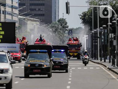 Petugas Dinas Pemadam Kebakaran Pemprov DKI melakukan penyemprotan cairan disinfektan di Jalan Thamrin, Jakarta, Selasa (31/3/2020). Penyemprotan yang dilakukan terus menerus itu untuk meminimalisir penyebaran COVID-19 di ruang udara dan ruas jalan. (Liputan6.com/Faizal Fanani)
