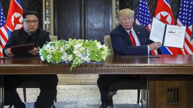 Donald Trump dan Kim Jong-un menandatangani perjanjian di Singapura. (AP/Evan Vucci)