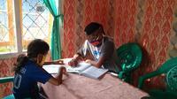 Foto : Eki Adsen, guru honorer di Kabupaten Manggarai Timur, NTT saat melakukan bimbingan belajar kepada siswanya di rumah (Liputan6.com/Ola Keda)