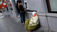 Seorang tunawisma duduk di samping mesin ATM di Paris, Prancis, Senin (5/2). (AP Photo / Francois Mori)