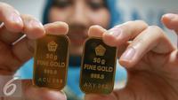 Seorang teller menunjukan emas batangan di Jakarta, Selasa (15/11). Harga emas batangan atau Logam Mulia milik PT Aneka Tambang Tbk (Antam) hari ini dibuka turun Rp 2.000/gram. (Liputan6.com/Angga Yuniar)