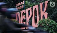 Pengendara motor bermasker memasuki kawasan Kota Depok, Jawa Barat, Minggu (12/4/2020). Menteri Kesehatan menyetujui menerapkan Pembatasan Sosial Berskala Besar (PSBB) di wilayah Kota Depok yang akan dimulai, Rabu (15/4) dalam pencegahan meluasnya COVID-19. (Liputan6.com/Helmi Fithriansyah)
