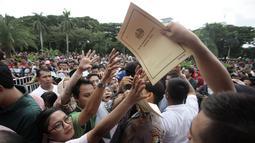 Warga berebut formulir untuk membuat paspor dalam acara Festival Keimigrasian 2018 di Lapangan Barat Daya Monas, Jakarta, Minggu (21/1). Dalam acara ini panitian menyediakan 1.600 formulir. (Liputan6.com/Arya Manggala)
