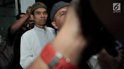 Ustaz Abdul Somad (UAS) berusaha menghindari kerumunan awak media setibanya di Kantor Majelis Ulama Indonesia (MUI), Jakarta, Rabu (21/8/2019). UAS memenuhi undangan MUI untuk menyampaikan klarifikasi mengenai video ceramahnya yang viral dan memicu polemik. (merdeka.com/Iqbal S Nugroho)