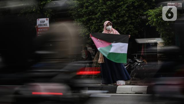 Masyarakat membawa bendera Palestina di jalan Basuki Rahmat, Jakarta, Kamis (20/5/2020). Aksi masyarakat tersebut untuk mengutuk penyerangan Israel ke Palestina yang telah menyebabkan ratusan korban jiwa. (Liputan6.com/Johan Tallo)